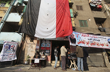 Supporters of parliamentary candidate El Maty of the Salafi party Al-Nour talk to people outside a polling station during parliamentary elections in Cairo
