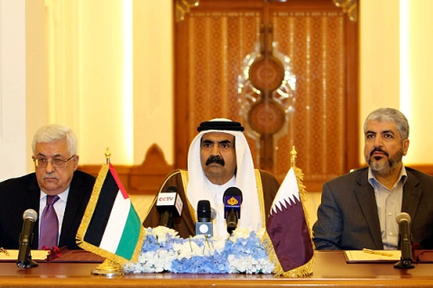 Palestinian President Abbas and Hamas leader Meshaal sit on either side of Qatar's Emir Sheikh Hamad during a meeting to sign an agreement in Doha
