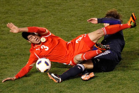 Japan's Otsuand and Bahrain's Alhayama fight for the ball at an Asian qualifying soccer match for the 2012 London Olympics Games in Tokyo