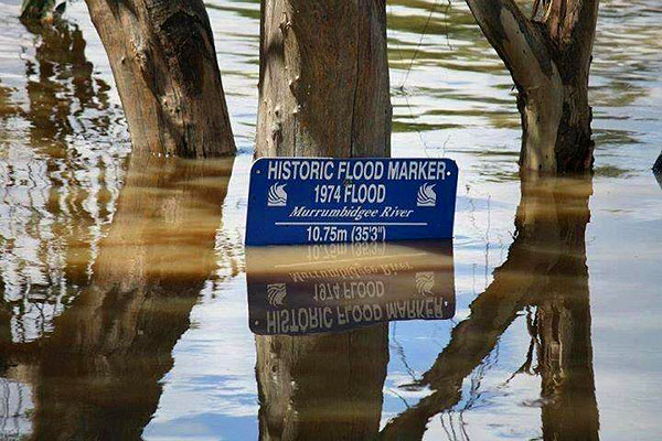 Flood waters rise against a historic flood marker