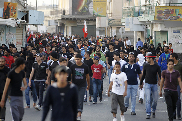 Hundreds of anti-government protesters walk from local streets towards the main highway to protest in the village of Diraz