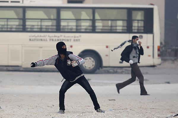 An anti-government protester throws stone at riot police during clashes in village of Diraz west of Manama