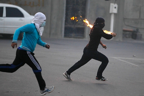 Anti-government protesters runs towards riot-police holding Molotov cocktails during clashes in the village of Diraz, west of Manama