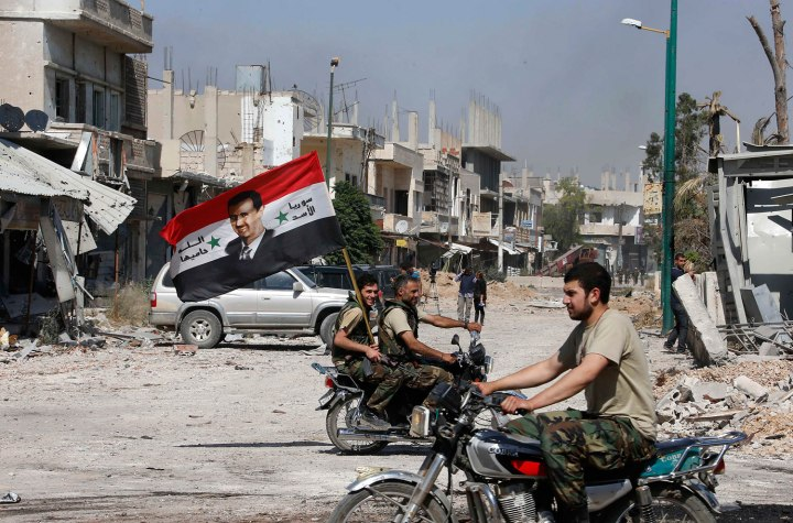 File photo of forces loyal to Syria's President Bashar al-Assad carrying the national flag as they ride on motorcycles in Qusair