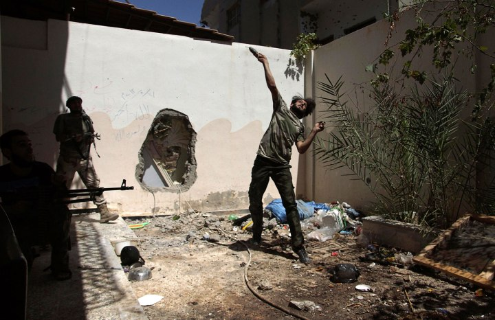 A Free Syrian Army fighter throws a homemade bomb towards forces loyal to Syria's President Bashar al-Assad as fellow fighters watch in Deir al-Zor