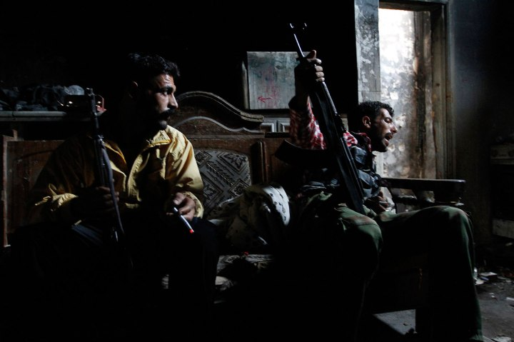 Free Syrian Army fighters carrying their weapons, sit inside a house in old Aleppo