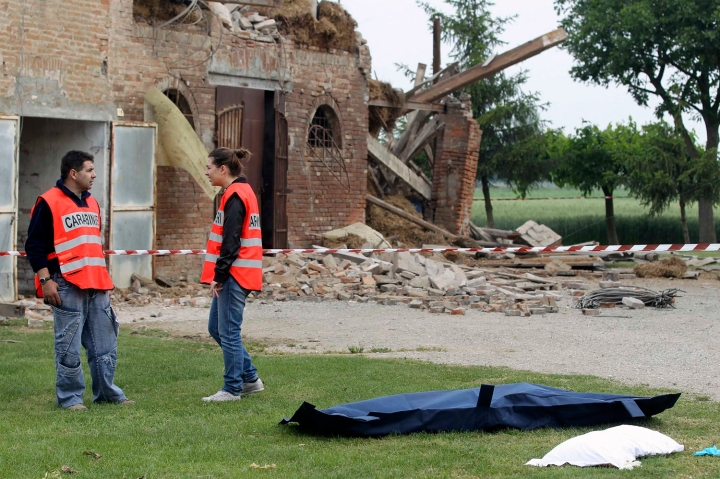Carabinieri paramilitary police officers stand beside the body of a woman after an earthquake in Sant' Agostino