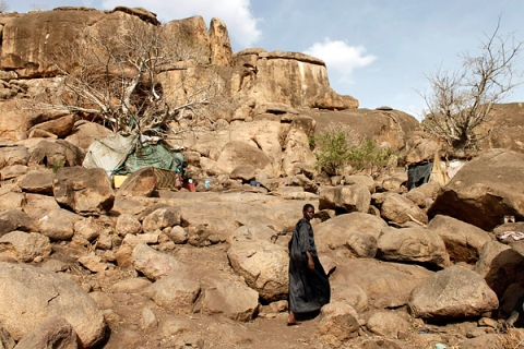 A woman walks towards a cave shelter in Bram village in the Nuba Mountains in South Kordofan