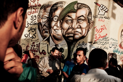 People walk under a grafitti depicting ousted president Hosni Mubarak, right.