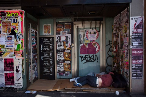 Two people sleep outside a closed down business in Madrid