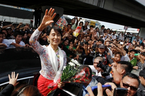 Myanmar's pro-democracy leader Aung San Suu Kyi greets migrant workers from Myanmar, as she visits them in Samut Sakhon province