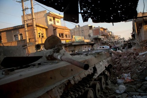 A destroyed Syrian forces tank remains in a damaged street in Atareb in northern Aleppo province on July 2, 2012.