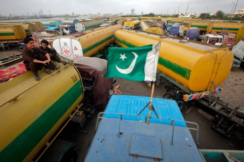 A Pakistan national flag is mounted on the top of a fuel tanker, which was used to carry fuel for NATO forces in Afghanistan, as drivers sit nearby, at a compound in Karachi