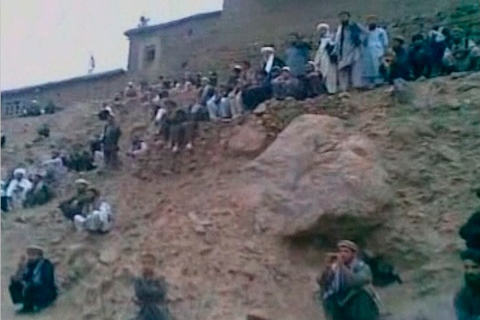 Men watch as an alleged member of the Taliban fires his rifle at a woman accused of adultery in this still image taken from undated footage released July 7, 2012.