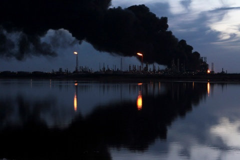 A column of smoke rises as fuel storage tanks are seen on fire at Amuay oil refinery in Punto Fijo in the Peninsula of Paraguana