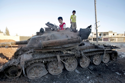 Syrian boys on a destroyed tank