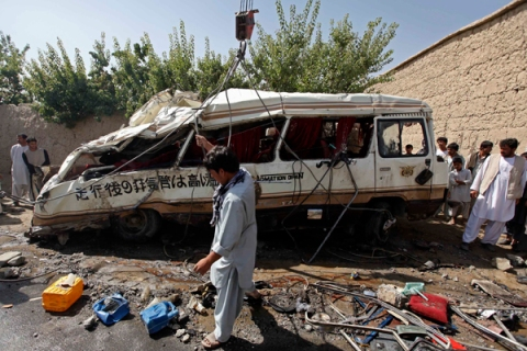 An Afghan man collects parts of a damaged bus, which was hit by a remote-controlled bomb, in the Paghman district of Kabul