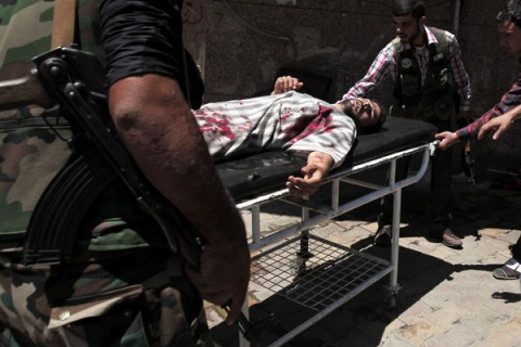 Syrian rebels rush a wounded man into a