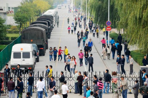 Workers walk past several paramilitary police vehicles near an entrance of a Foxconn Tech-Industry Park in Taiyuan