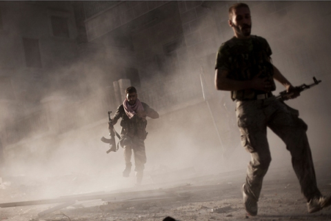 Free Syrian Army fighters run after attacking a Syrian Army tank during fighting in  Aleppo, Syria on Sept 7, 2012.