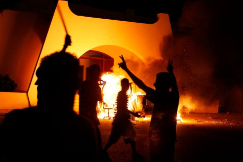 Demonstrators celebrate after burning a car as they stormed the headquarters of the Islamist Ansar al-Sharia militia group in Benghazi
