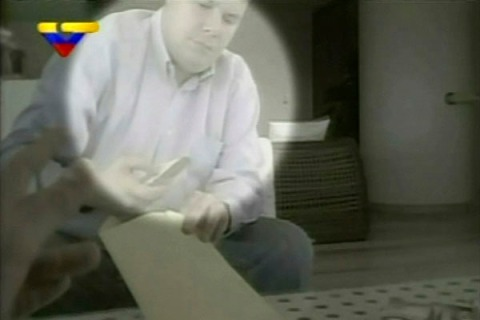 This undated still image taken from video by state television station VTV shows opposition lawmaker Juan Carlos Caldera receiving money from an unidentified man