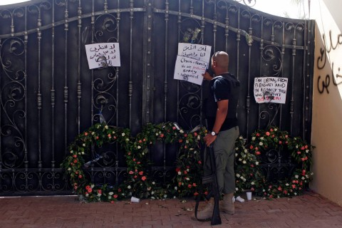 A Libyan government militia guarding the main entrance of the U.S. consulate that was attacked last week, fixes a note written by Libyans against the attack, in Benghazi