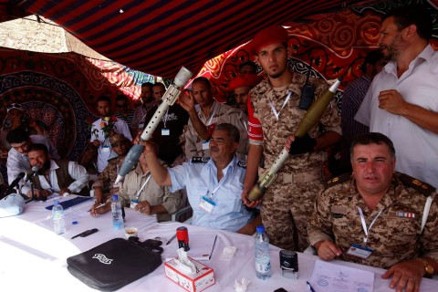Members of the Libyan military hold weapons and ammunition handed over to them by civilians in Tripoli's Martyrs' Square