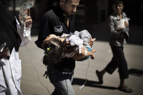 A Syrian man carries his wounded daughter outside a hospital in the northern city of Aleppo on September 18, 2012.