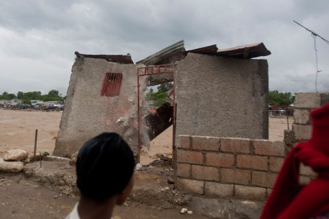 Residents look at a damaged house on the shore of a river after heavy rains brought by Hurricane Sandy in Port-au-Prince, Haiti, on Oct. 25, 2012.