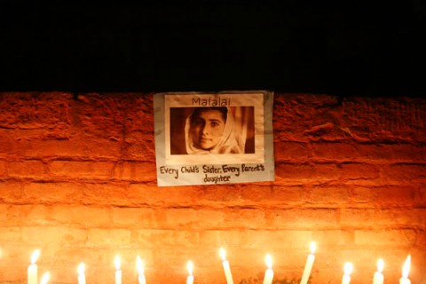 Candles are lit in front of portrait of Pakistani schoolgirl Yousafzai