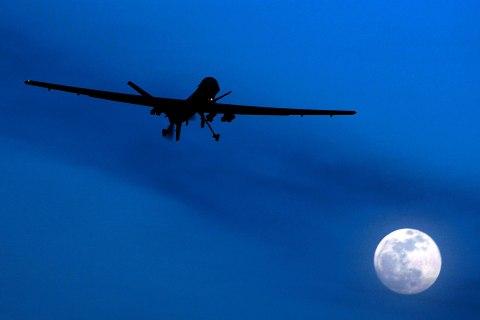 image: A U.S. Predator drone flies over the moon above Kandahar Air Field, southern Afghanistan, Jan. 31, 2010.