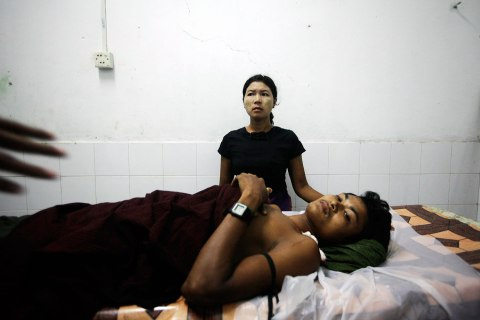 image: A woman stands by her brother, who was injured during the recent sectarian violence, at a hospital in Kyuktaw township, Oct. 25, 2012.