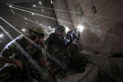 image: Rebel fighters belonging to the Javata Harria Sham Qatebee watch over the enemy position during skirmishes at the first line of fire in Karmal Jabl neighborhood, district of Arkup, Aleppo, Oct. 21, 2012.