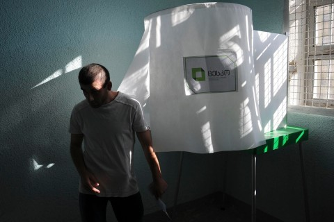Inmate leaves voting booth during parliamentary election at polling station at Gldani prison No. 8 in Tbilisi