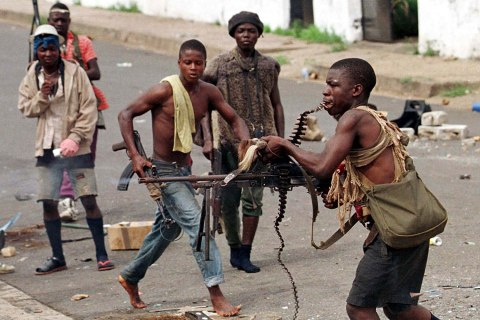 A street fighter with Charles Taylor's NPFL fires his machine gun while holding the string of bullet..