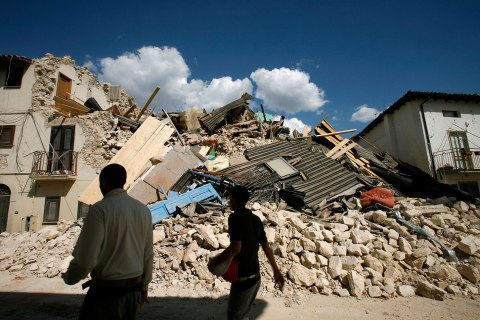 image: Residents walk past destroyed houses after an earthquake in the Italian village of Onna, Aquila, April 6, 2009.
