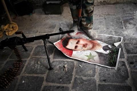 FSA fighter stands on a poster of President Bashar Assad