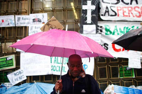 A member of the Mortgage Victims' Platform awaiting an eviction order, stands under an umbrella outside Bankia bank headquarters in Madrid