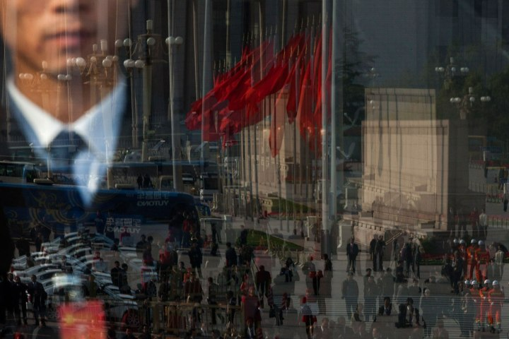 Journalists, firemen, buses, and red flags on Tiananmen are reflected in a glass door of the Great Hall of the People
