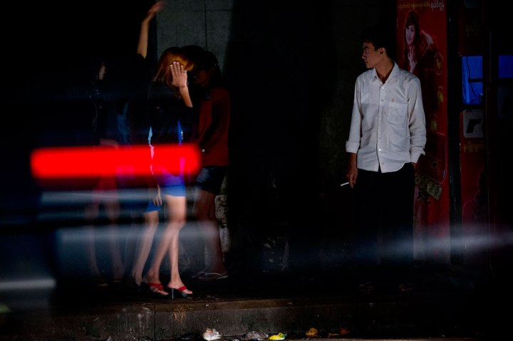 A man looks at female sex workers by the side of a road while a car drives by in Yangon, Myanmar.