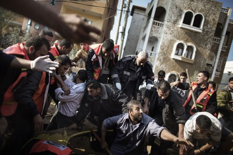 A Palestinian man calls for help as he and others try to save a man  trapped under his car just after an Israeli air raid