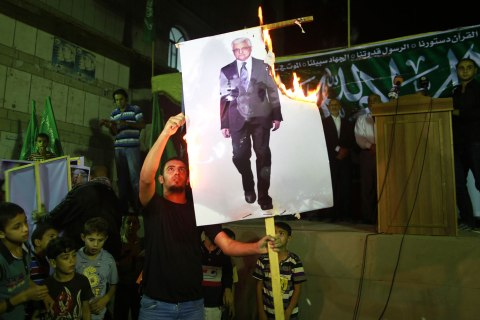 A Hamas supporter burns a poster depicting Palestinian President Mahmoud Abbas during a protest in Jabalya in the northern Gaza Strip