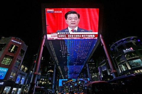 image: A huge screen shows a broadcast of Chinese President Hu Jintao speaking at the opening session of the 18th Communist Party Congress at the Great Hall of the People in Beijing, China, Nov. 8, 2012.