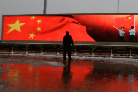 image: A Chinese man stands near a screen displaying the Chinese national flag and Chinese paramilitary police men performing a flag ceremony near the Great Hall of the People where the Chinese Communist Party's 18th National Congress is scheduled to begin on Nov. 8 in Beijing, Nov. 4, 2012.