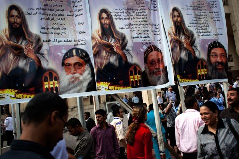 image: Egyptian Copts walk past an election poster with pictures of the three candidates, Father Raphael Ava Mina, left, Anba Tawadros, center and Anba Raphael, right following the papal election ceremony at the Coptic Cathedral in Cairo, Nov. 4, 2012.