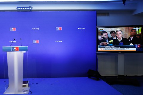 image: An empty podium is seen at the headquarters of the UMP politial party in Paris as a news programme airs an interview with former prime minister Francois Fillon on a large-screen television after the closing of the polls Nov. 18, 2012.