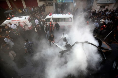image: Palestinians extinguish the fire after an Israeli air strike on a car carrying Hamas's military chief Ahmed Al-Jaabari in Gaza City, Nov. 14, 2012.