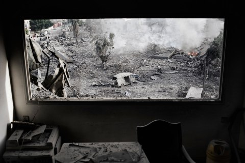 image: A leveled Hamas government office is seen through the window of a nearby building following Israeli air strikes in Gaza City, Nov. 21, 2012.