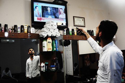 image: A barber watches the results of the U.S. presidential election in Istanbul, Nov. 7, 2012.